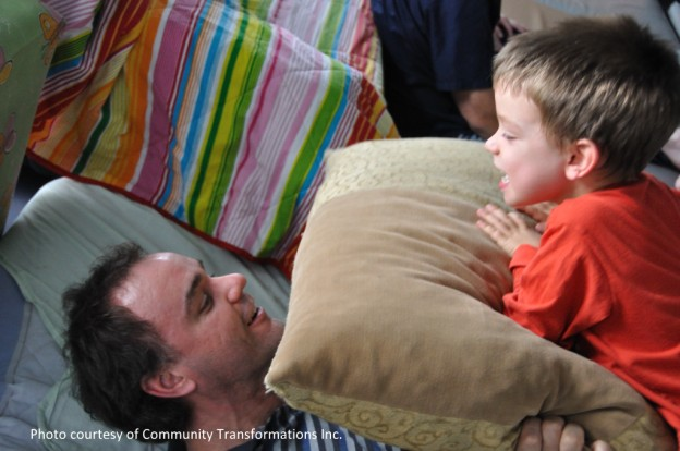 Father and Son playing together ith big pillow.