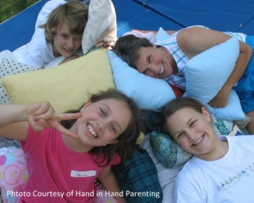 Family of mother with teen/preteen children lounging with pillows