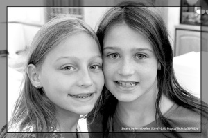 Pre-Teen sisters smile at the camera.