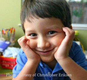 Smiling boy with chin resting on hands, with school room behind him.