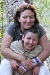 Mum and Boy, smiling at camera, hugging