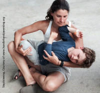 Child has a tantrum in arms of mother. Parenting by Connection