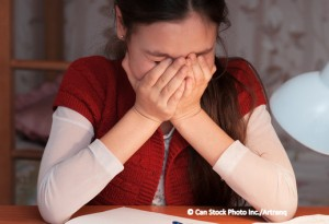 Girl covers face in frustration with homework.
