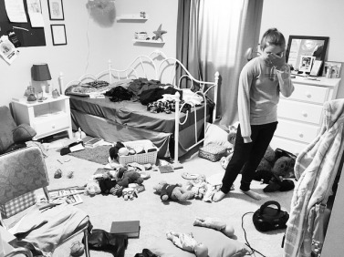 A teen girl stands in the middle of a very messy room, hand over her face.